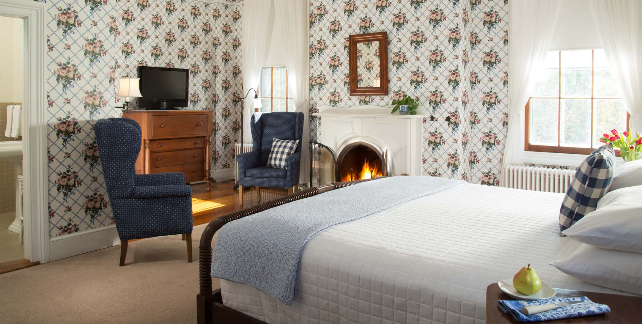 King bed in the Blue Room at Brampton Inn with a sitting area for two