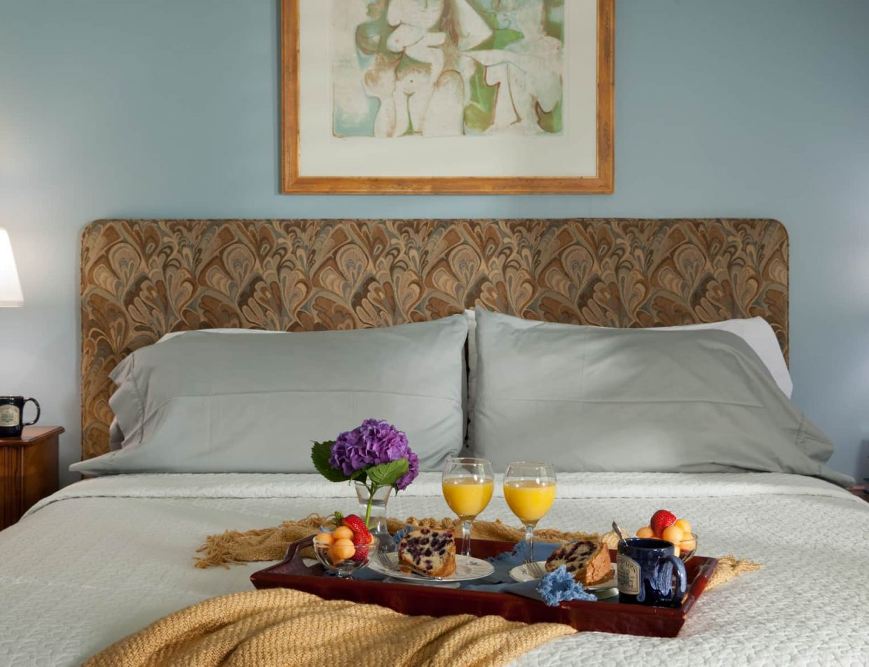 A tray of breakfast on a king bed in Robin's Nest at Brampton Inn