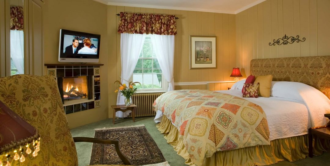 King bed in a room with warm earth-toned walls and a fireplace