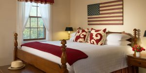 King bed in the Red Room at Brampton Inn with an American Flag wall art