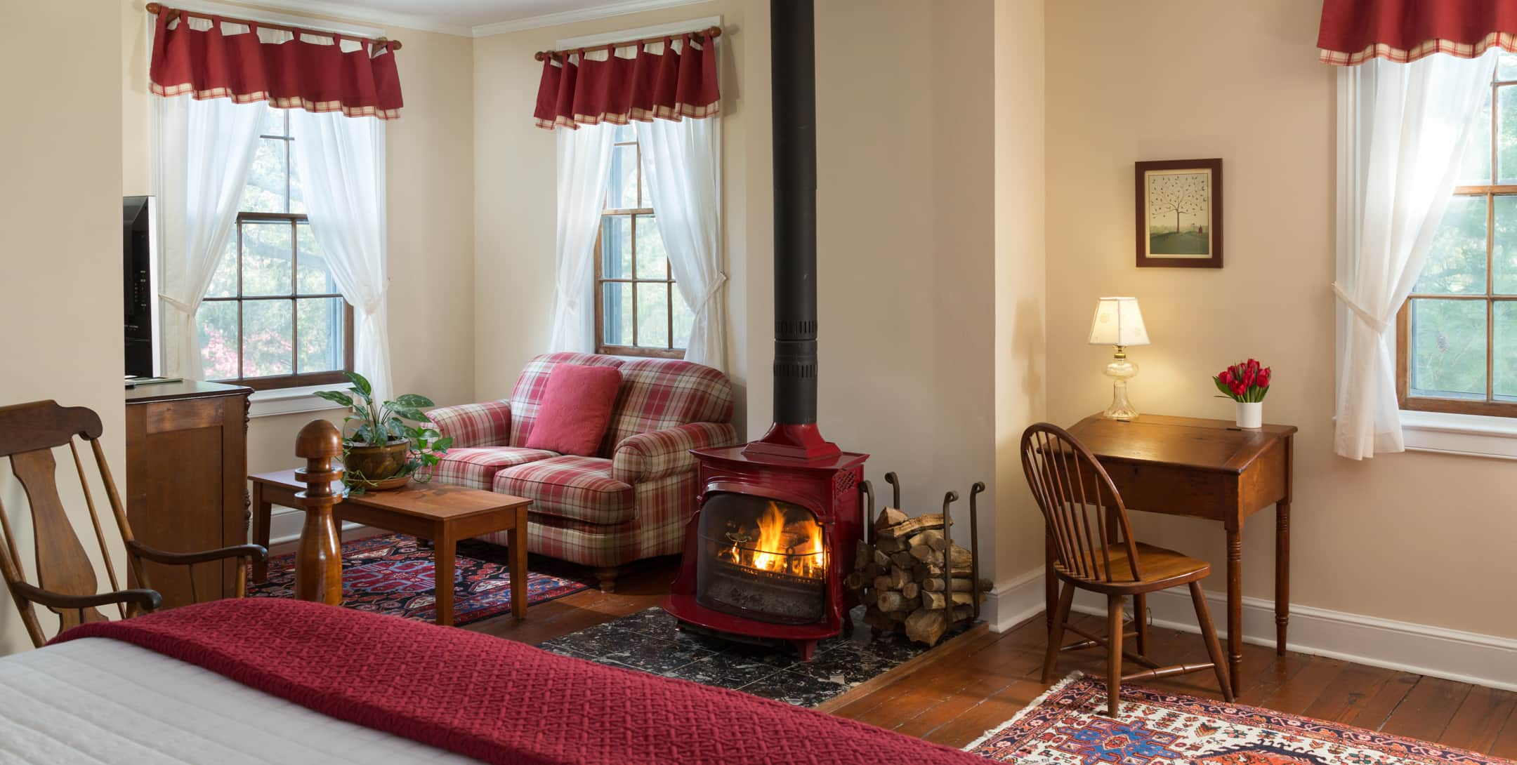 Red Room at Brampton Inn with a sitting area and a wood-burning stove and a writing desk