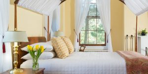 The Yellow Room at Brampton Inn with a queen bed and fireplace