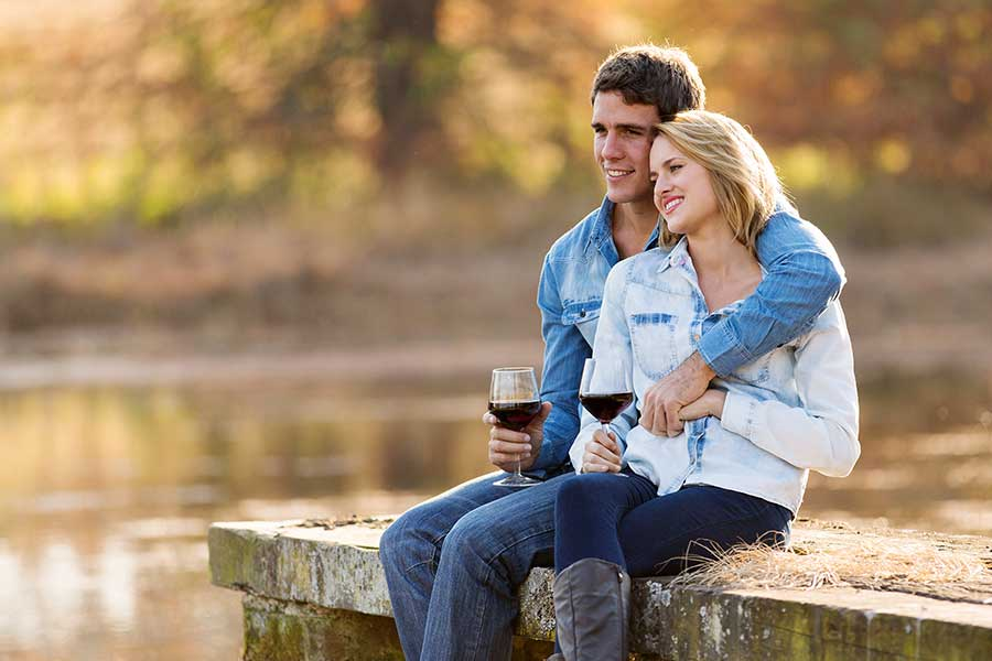 Couple sitting on dock drinking red wine