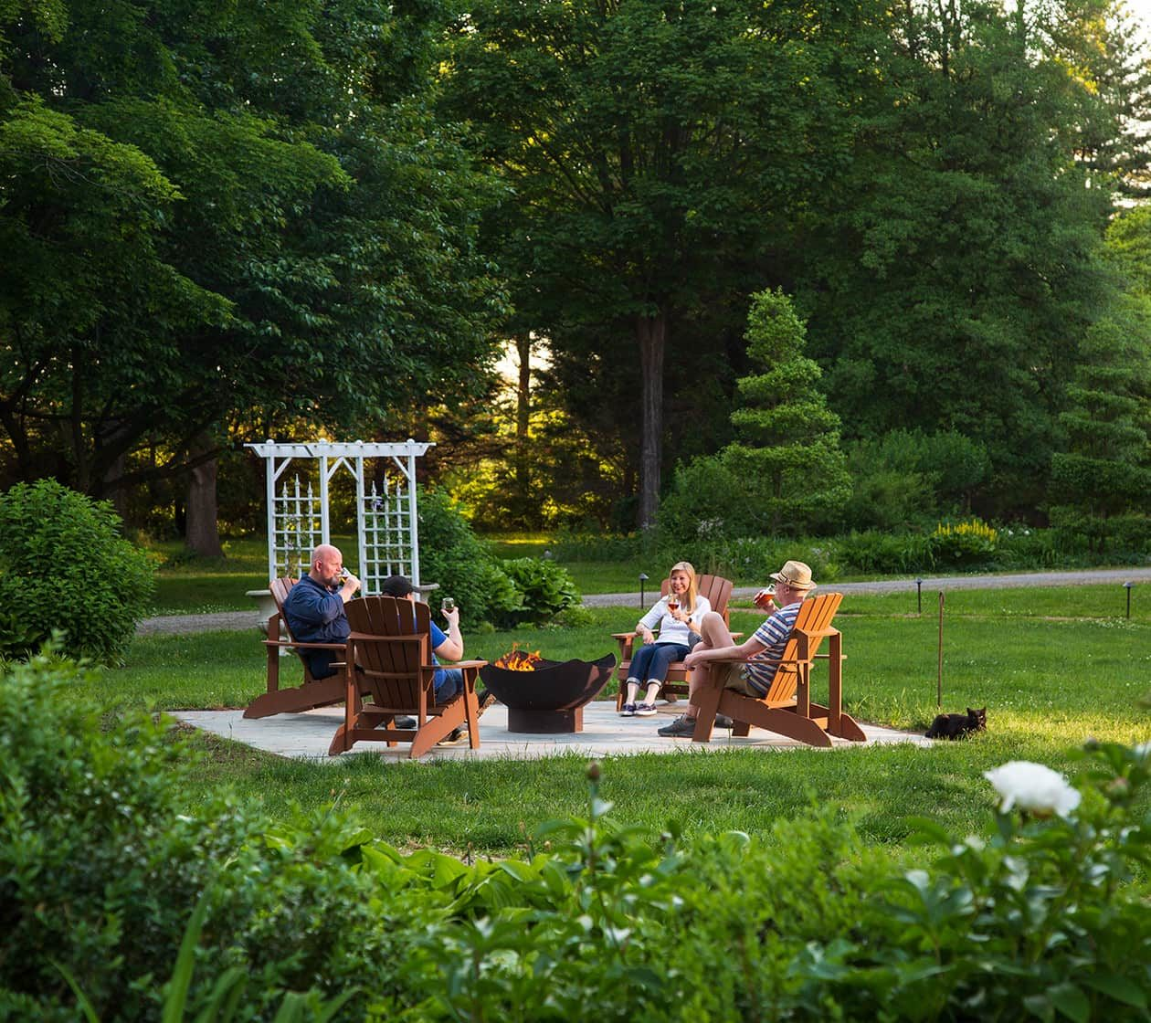 A group of friends gather around a fire pit and roast hotdogs