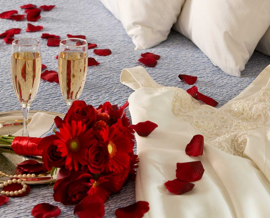 Champagne, bouquet of red flowers and wedding dress