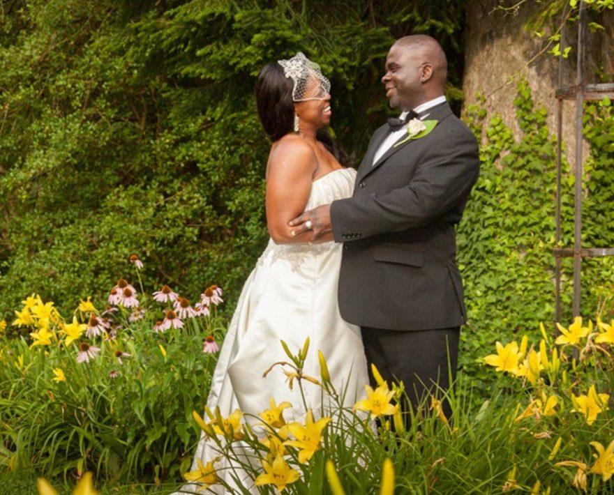 Bride and groom standing in garden of yellow flowers
