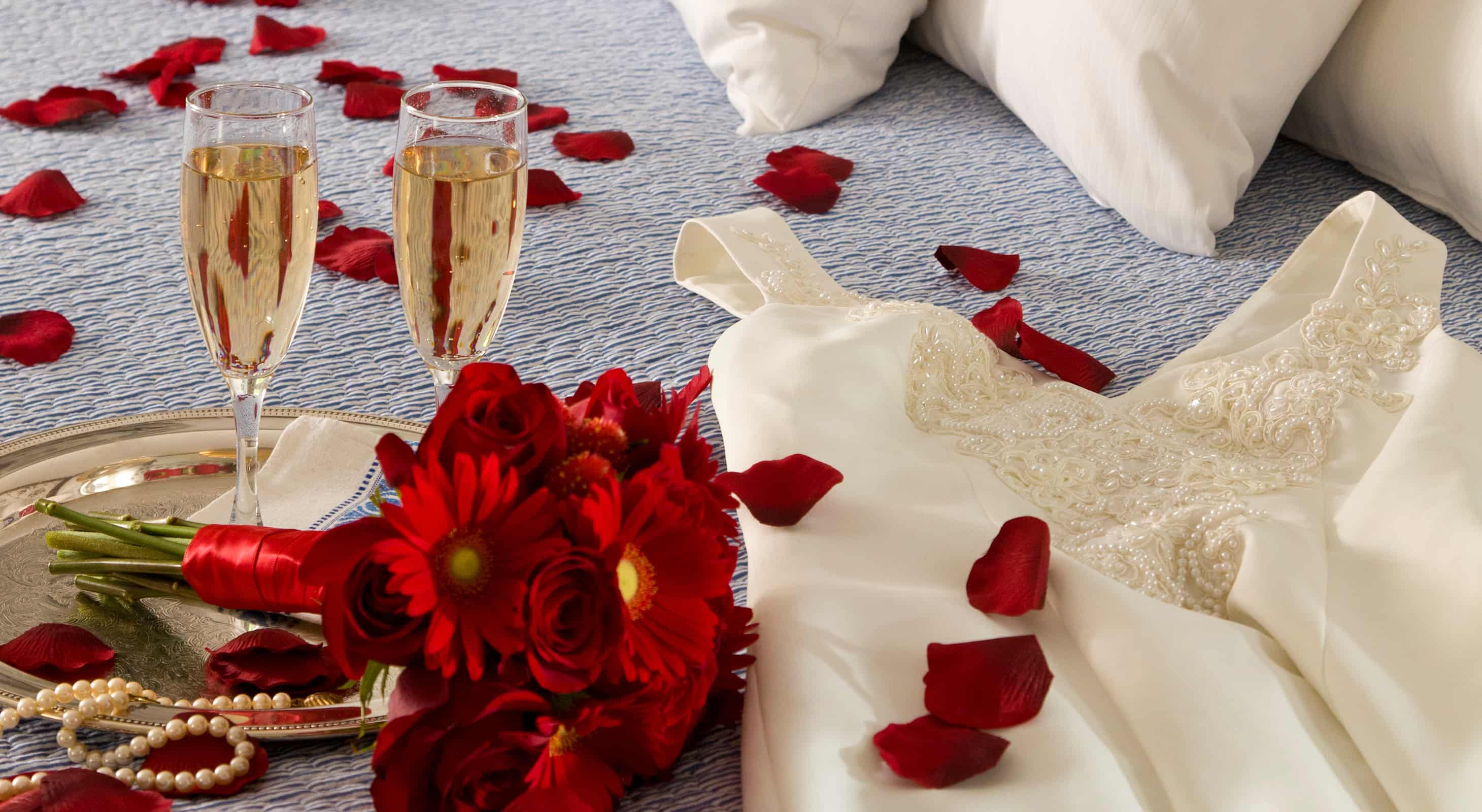 Champagne, flowers and wedding dress on bed
