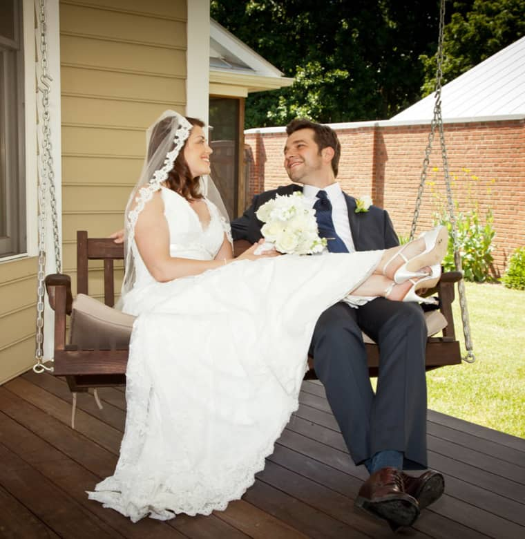 Bride and Groom lounging on a bench swing