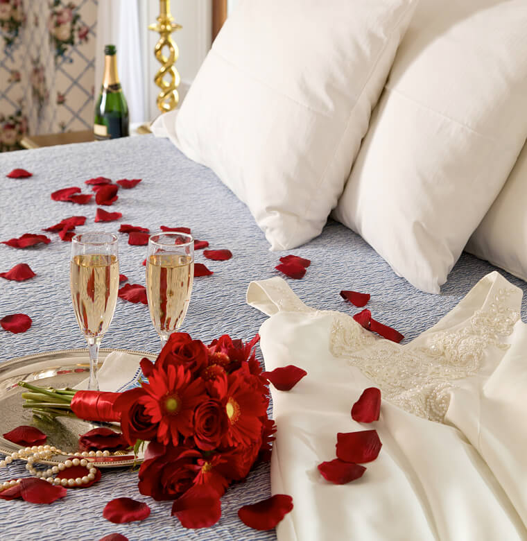 romance with red flowers and Champagne on bed
