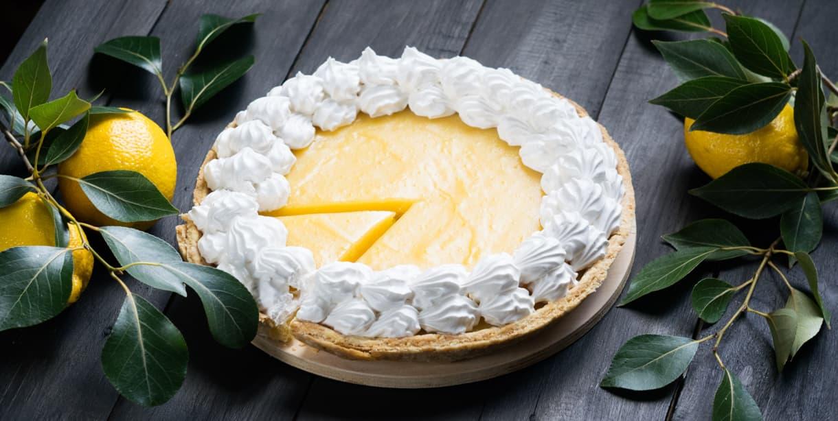 A lemon meringue pie on a table with lemons