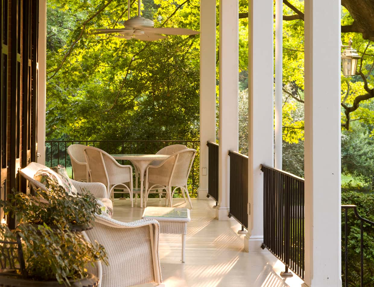 Covered porch with seating for two at Brampton Inn