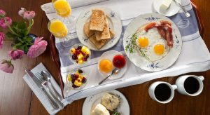 Breakfast tray with eggs, toast, fruits, coffee, etc.