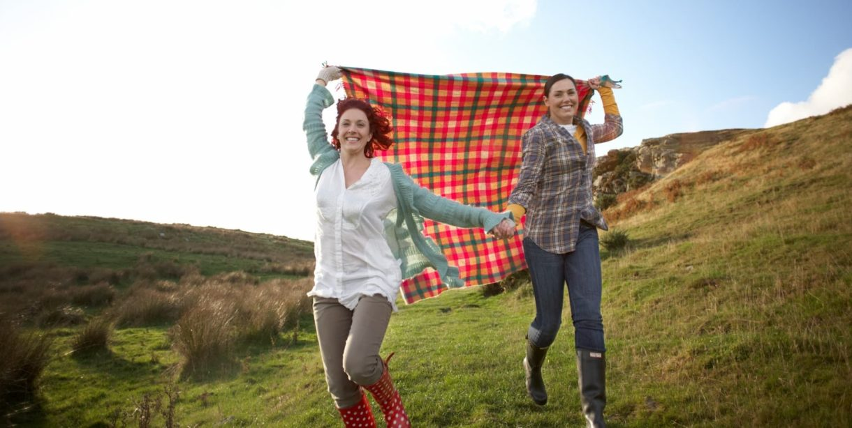 couple running with picnic blanket