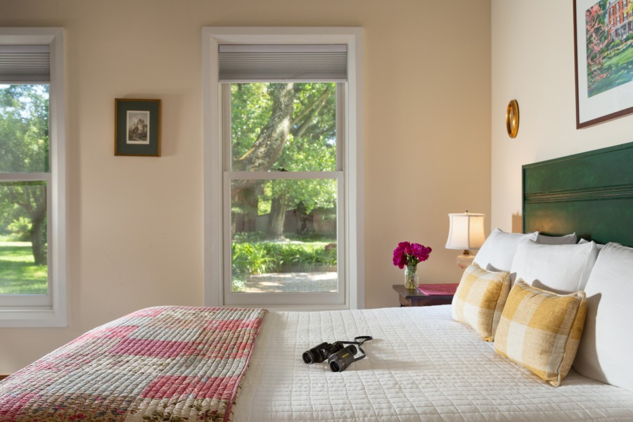 Spacious guest room with windows overlooking the green gardens